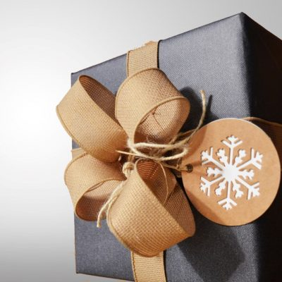 Bow tied gift box wrapped in brown paper.